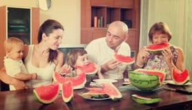 Gelukkige familie samen met watermeloen over eettafel stock fotografie
