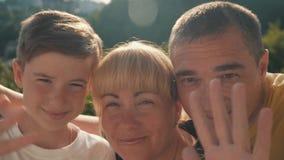 Gelukkige familie Skype Zij zeggen Hello en glimlach, bekijken de camera en golven hun handen Moeder, zoon en vader stock video