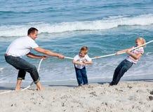 Gelukkige familie speeltouwtrekwedstrijd Stock Afbeeldingen
