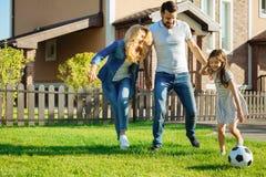 Gelukkige familie speelvoetbal in de werf stock afbeelding