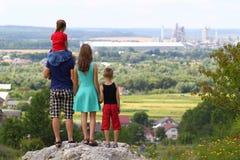 Gelukkige familie status die zich op een rots in bergen bevindt Concept o Royalty-vrije Stock Afbeeldingen