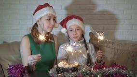 Gelukkige familie, twee meisjes, klein en een tiener in de hoed van Santa Claus met aangestoken sterretjes bij de cakezitting op stock footage