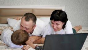 Gelukkige familie: vader, moeder en baby, het liggen op bed, het bekijken laptop, het glimlachen en het lachen stock video
