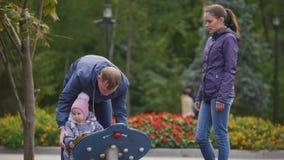 Gelukkige familie: Vader, Moeder en kind - meisje die in de herfstpark lopen: het mamy, papa en baby spelen bij speelplaats stock footage