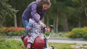 Gelukkige familie: Vader, Moeder en kind - meisje die in de herfstpark lopen: mamma en baby het spelen bij speelplaats stock footage
