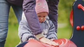 Gelukkige familie: Vader, Moeder en kind - meisje die in de herfstpark lopen: moeder en baby het spelen bij speelplaats stock footage