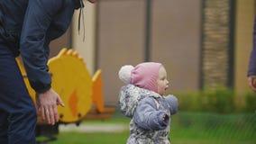 Gelukkige familie: Vader, Moeder en kind - meisje die in de herfstpark lopen: papa en baby het spelen bij speelplaats stock video