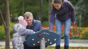 Gelukkige familie: Vader, Moeder en kind - meisje die in de herfstpark lopen: vader en baby het spelen bij speelplaats stock videobeelden