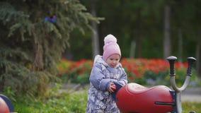 Gelukkige familie: Vader, Moeder en kind - meisje die in de herfstpark lopen: vader en baby het spelen bij speelplaats stock footage