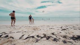 Gelukkige familie van drie die een bal op het strand spelen stock footage
