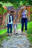 Gelukkige familie van drie die het de herfstpark lopen stock foto's