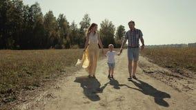 Gelukkige familie van drie die in het platteland samen lopen stock footage