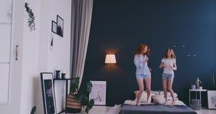 Gelukkige familie van leuke dochter en jonge moeder die en op bed springen dansen terwijl pret thuis tijdens vakantie hebben stock videobeelden