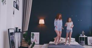 Gelukkige familie van leuke dochter en jonge moeder die en op bed springen dansen terwijl pret tijdens ochtend op vakantie bij he stock video