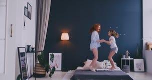 Gelukkige familie van leuke dochter en jonge moeder die en op bed springen dansen terwijl pret tijdens ochtend op vakantie bij he stock footage