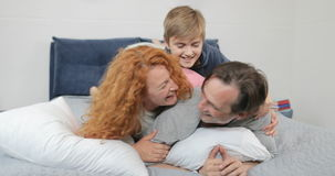 Gelukkige familie in van slaapkamerkinderen en ouders mededeling die samen over vader op bed in ochtend liggen stock videobeelden
