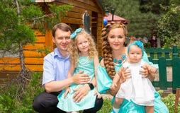 Gelukkige familie van vader, moeder en twee kinderen in openlucht op een de zomerdag Portretouders en jonge geitjes op aard Posit Royalty-vrije Stock Foto's