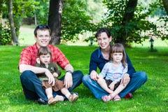 gelukkige familie van vier die op gras zitten Stock Fotografie