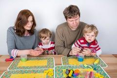 Gelukkige familie van vier die pret hebben thuis Stock Afbeelding