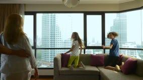 Gelukkige familie, vrouw, man en twee kinderen met een koffer op de achtergrond van wolkenkrabbers in een panoramisch venster stock videobeelden