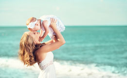 Gelukkige familie in witte kleding De moeder werpt op baby in de hemel