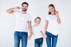 Gelukkige familie in witte t-shirts die tanden met tandenborstels schoonmaken stock afbeelding