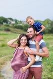 Gelukkige familie: zwanger mamma, papa met zoon stock foto