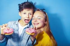 Gelukkige familiebroer en zuster die donuts op blauwe achtergrond eten, het concept van levensstijlmensen, jongens en meisjes het royalty-vrije stock foto's
