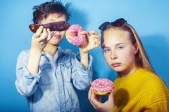 Gelukkige familiebroer en zuster die donuts op blauwe achtergrond eten, het concept van levensstijlmensen, jongens en meisjes het stock afbeelding