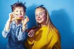 Gelukkige familiebroer en zuster die donuts op blauwe achtergrond eten, het concept van levensstijlmensen, jongens en meisjes het royalty-vrije stock fotografie