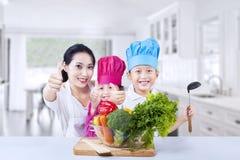 Gelukkige familiechef-kok en groente thuis Stock Foto's