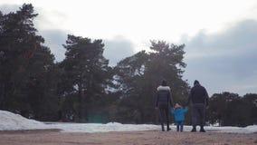 Gelukkige familiegangen in de winter bosouderschap, seizoen en mensenconcept stock footage