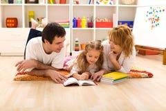 Gelukkige familielezing in de jonge geitjesruimte Stock Foto's