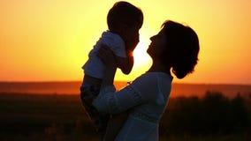 Gelukkige familiemamma en zoon op het gebied bij zonsondergang stock videobeelden