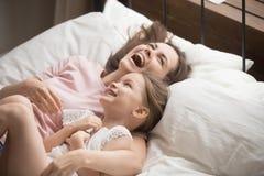 Gelukkige familiemoeder die jong geitjedochter lachen omhelzen die op bed liggen royalty-vrije stock foto's