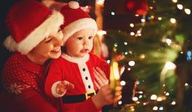 Gelukkige familiemoeder en baby dichtbij Kerstboom in vakantie nigh Stock Foto