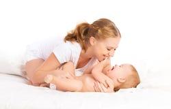 Gelukkige familiemoeder en baby die pret spelen hebben, die op bed lachen Stock Fotografie