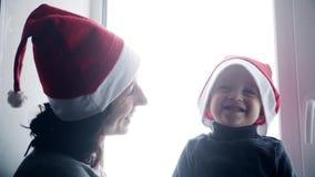 Gelukkige familiemoeder en baby die thuis wit venster spelen voor Kerstmis Vrolijke jongen en vrouw in Santa Claus-hoed stock videobeelden
