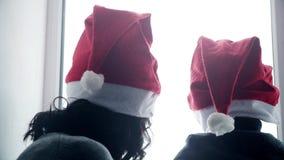 Gelukkige familiemoeder en baby die thuis wit venster spelen voor Kerstmis Vrolijke jongen en vrouw in Santa Claus-hoed stock video