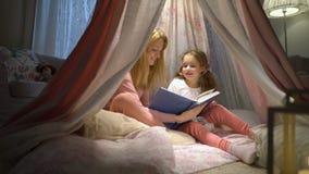 Gelukkige familiemoeder en haar weinig dochter die een boek in een tent thuis lezen stock video
