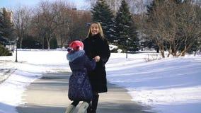 Gelukkige familiemoeder en kinddochter die pret hebben, die bij de wintergang in openlucht spelen stock video