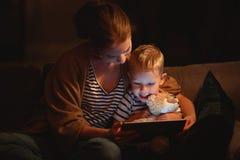gelukkige familiemoeder en kindzoon met tablet in avond stock afbeelding