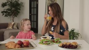 Gelukkige familiemoeder en kleine leuke dochter twee die ontbijt van zitting op lijst genieten stock video