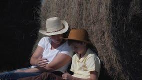 Gelukkige familiemoeder en zoon met een tabletzitting op het gebied, die op een hooi-broodje leunen Het concept een gelukkige fam stock video