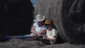 Gelukkige familiemoeder en zoon met een tabletzitting op het gebied, die op een hooi-broodje leunen Het concept een gelukkige fam stock footage