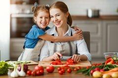 Gelukkige familiemoeder met kindmeisje die plantaardige salade voorbereiden stock afbeeldingen