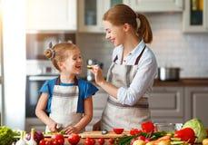Gelukkige familiemoeder met kindmeisje die plantaardige salade voorbereiden royalty-vrije stock foto's