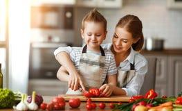 Gelukkige familiemoeder met kindzoon die plantaardige salade voorbereiden stock afbeeldingen