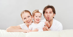Gelukkige familiemoeder, vader, de dochter van de kindbaby thuis op en bank die spelen lachen Stock Afbeelding