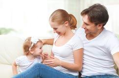 Gelukkige familiemoeder, vader, de dochter van de kindbaby thuis op en bank die spelen lachen Stock Fotografie